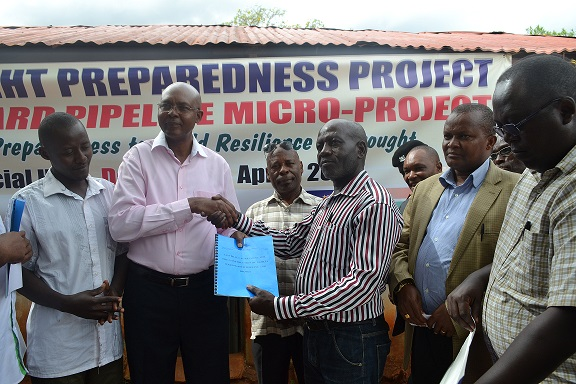 Taita Taveta Governor hands over contract agreement to the contractor during the launch of the Ngolia Drought Preparedness Project